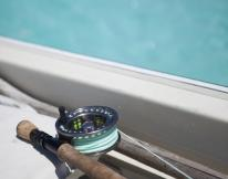 fly fishing rod on boat with turquoise waters behind