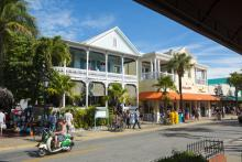 lively duval street key west with pedestrians, scooters, and bikes